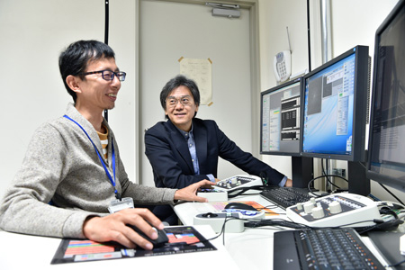 Prof. Kato (left) and Prof. Namba operating the CRYO ARMTM from a separate room